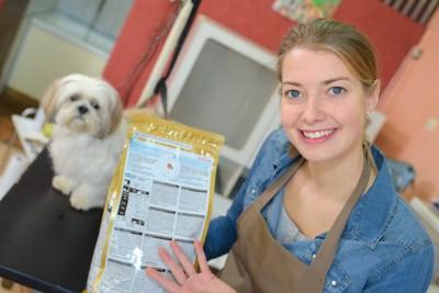 ドッグフードの表示を見せる女性の店員と犬