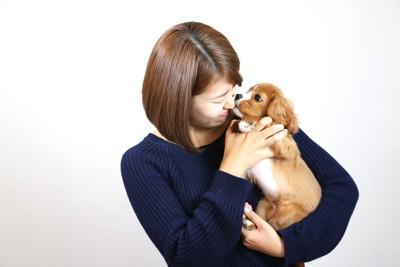 子犬を抱っこして見つめる女性