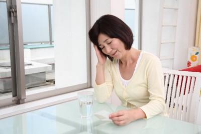 中年女性 頭を抱え 薬