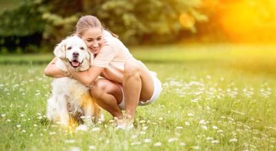 草原で犬を抱きしめる女性