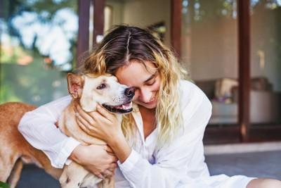 犬を抱きしめる金髪の女性
