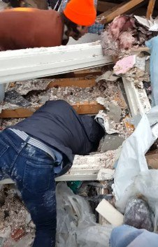 瓦礫の中にもぐる人