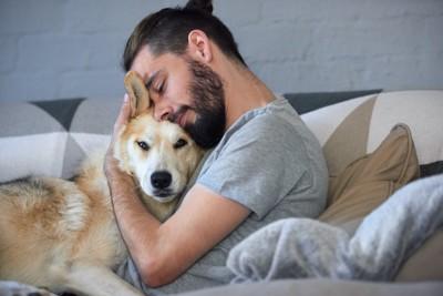 ソファーで男性に抱きしめられる犬
