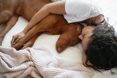 犬を抱きしめて一緒に眠る女性