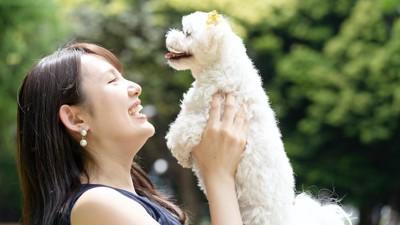犬を抱き上げる笑顔の女性
