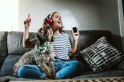 音楽に合わせて歌う女性と犬