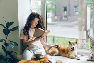 窓辺で本を読む女性と隣に座る柴犬