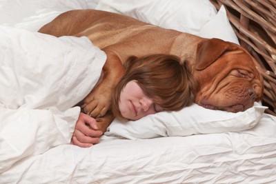 一緒のベッドで犬にハグされて眠る子供