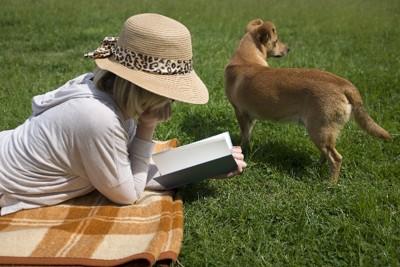 原っぱで読書する女性と犬
