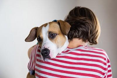 抱きしめられた女性の肩に顔を乗せている犬
