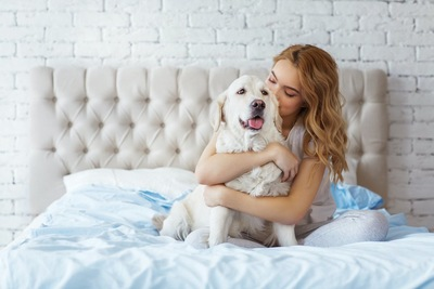 ベッドの上で犬にハグをする女性