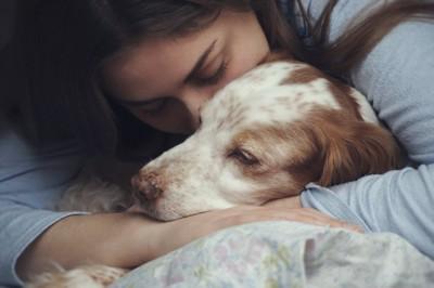 横になった犬を抱きしめる女性