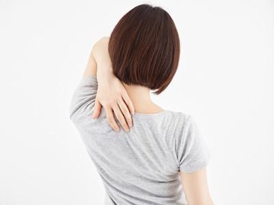 肩甲骨を抑える女性