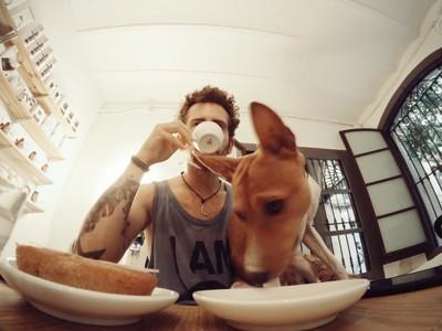 犬と一緒に食事する男性