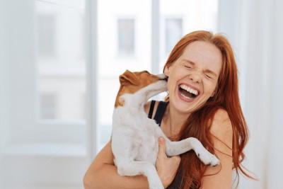 犬に耳を舐められて笑う女性