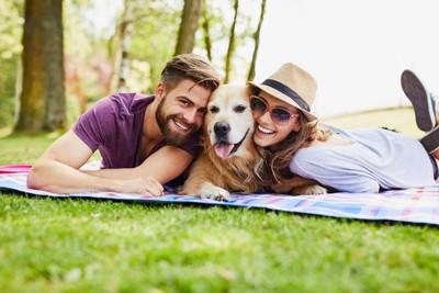 ピクニックを楽しむ男女と犬