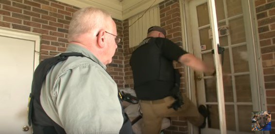 ドアを蹴り開ける警官