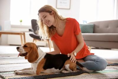 女性の隣でリラックスする犬