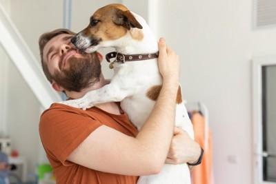 男性の顔を舐める犬