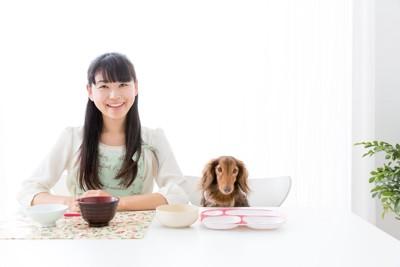 食事する女性と犬
