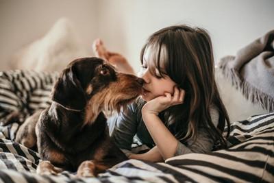 ベッドで犬とキスをする女の子