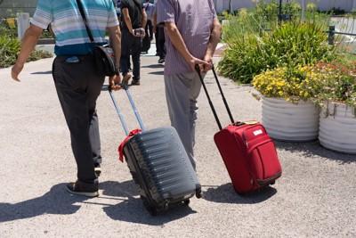 キャリーケースを引いて歩く2人の男性