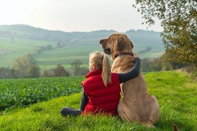 肩を組む女の子と犬の後ろ姿