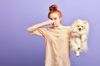 片手で犬を抱えて鼻をつまんでいる女性