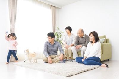 リビングで子供と遊ぶ犬と家族