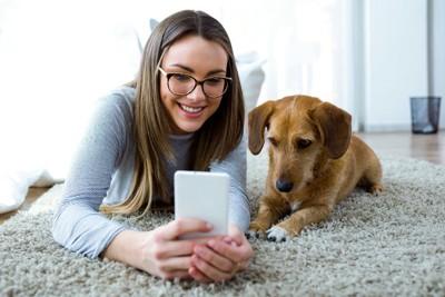 女性とスマホを見る犬