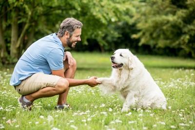 笑顔の男性にお手をする犬