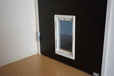 黒いドアに取り付けられた白いペットドア