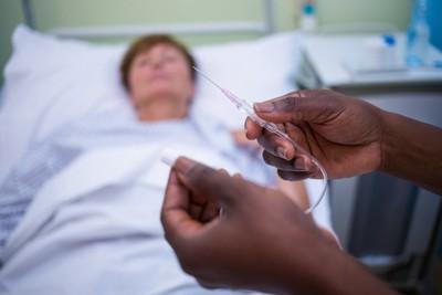 入院患者と点滴を準備するナースの手