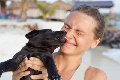 女性にキスする黒い子犬