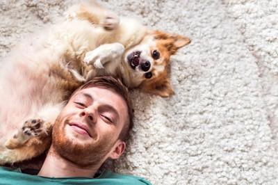 仲良く寝転ぶ男性と犬