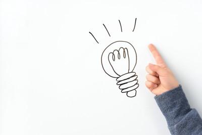 電球の絵と指差す人の手