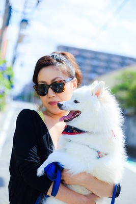 女性に抱っこされている白い犬
