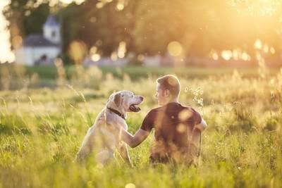 夕焼けの中で寄り添って座る男性と犬