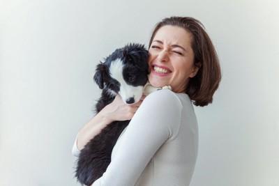 笑顔の女性に抱っこされるボーダーコリーの子犬