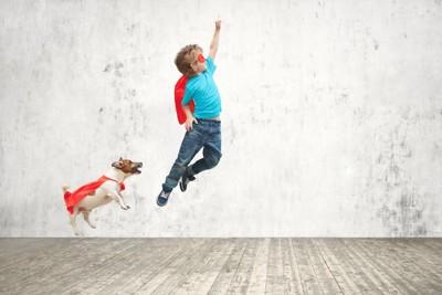 ジャンプする男の子とジャック・ラッセル・テリア