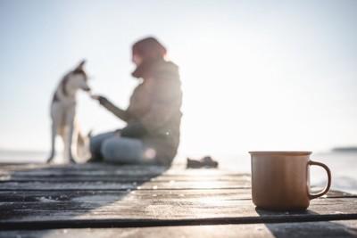 マグカップと犬と女性