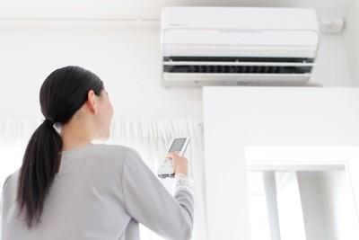 エアコンをつける女性
