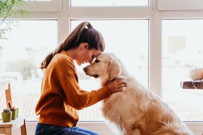 おでこをくっつけ合う女性と犬