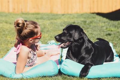 日光浴を楽しむ少女と犬