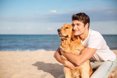 飼い犬を後ろから抱きしめる男性