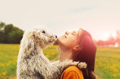 犬を抱き上げる女性と犬