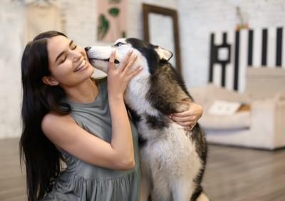 女性にキスをする犬
