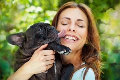 女性の口を舐める犬