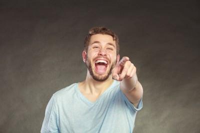 指をさして笑う男性