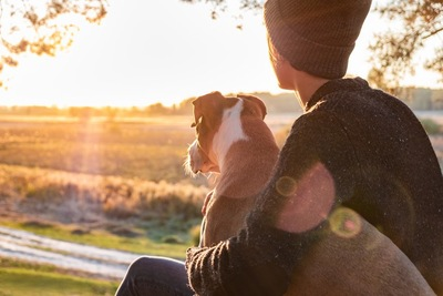 犬を抱いている女性の後ろ姿